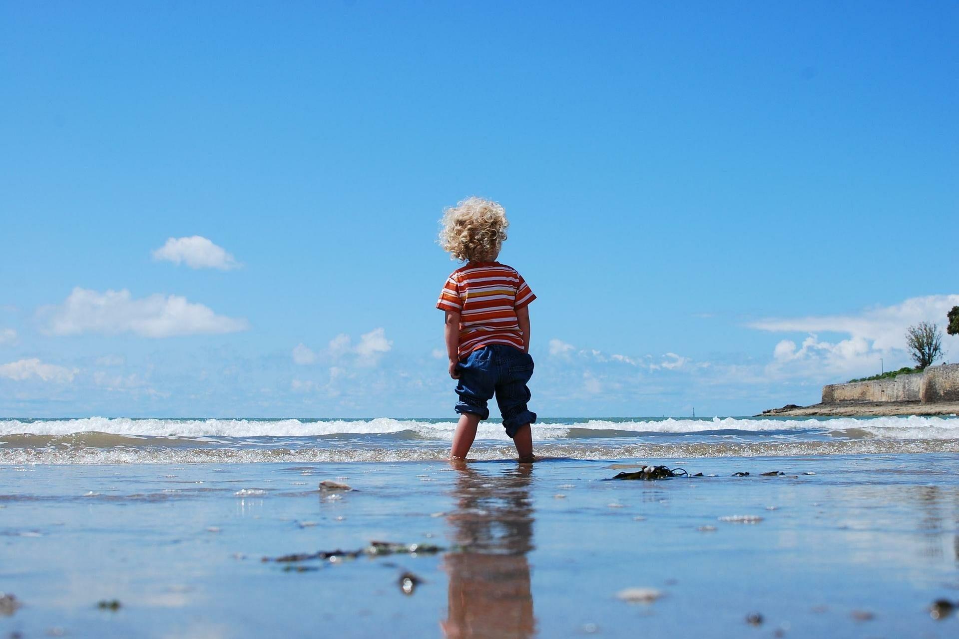 Kind am Strand von hinten